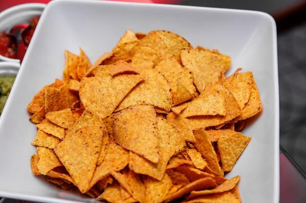 Meksykańskie chipsy kukurydziane w białym kubku, przekąska tortilla