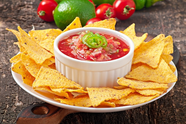 Meksykańskie chipsy nacho i salsa zanurzone w misce na drewnianym