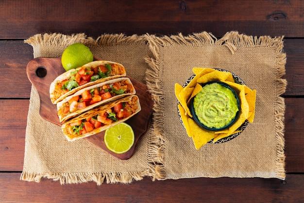 Meksykańskie chipsy nachos i tacos z mięsem i warzywami. tacos, limonki i chili na drewnianych deskach. taco z mięsem, pomidorami i ziołami