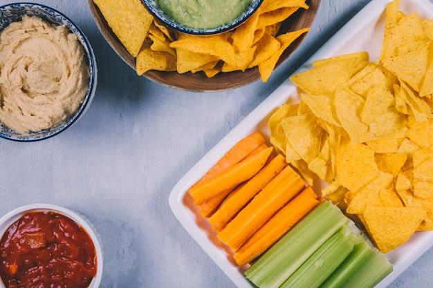 Meksykańskie chipsy nachos; marchewka z pędami selera w zasobniku z sosem salsa w misce