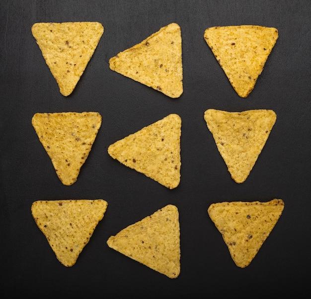 Meksykańskie chipsy nachos na czarnym tle chipsy nachos przekąski tapety widok z góry