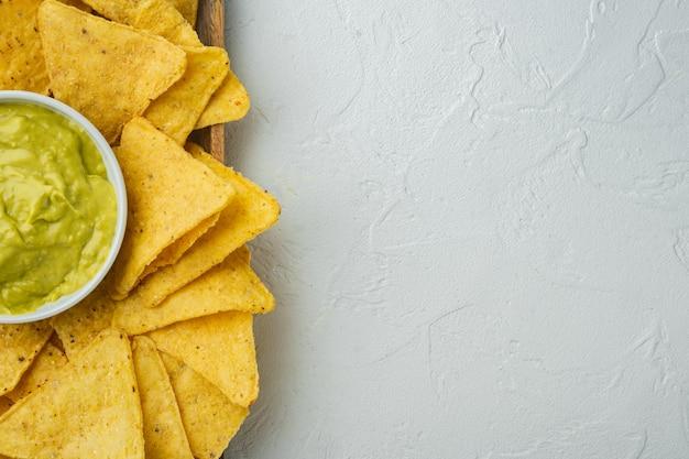 Meksykańskie chipsy nachos z sosami serowymi i guacamole, na białym stole, widok z góry lub flat lay