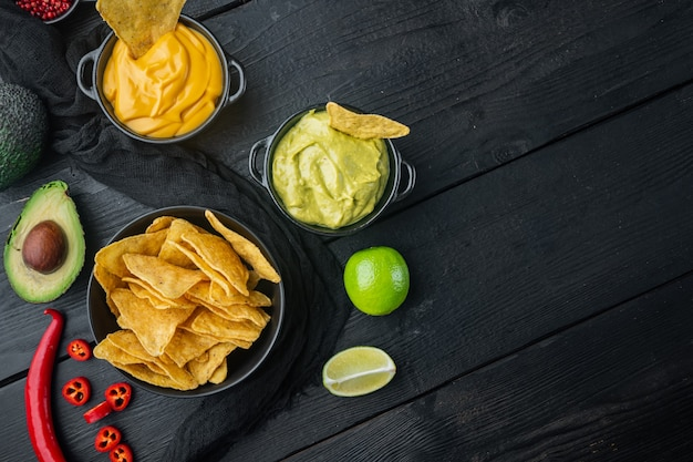 Meksykańskie chipsy nachos z sosami serowymi i guacamole, na czarnym drewnianym stole, widok z góry lub na płasko