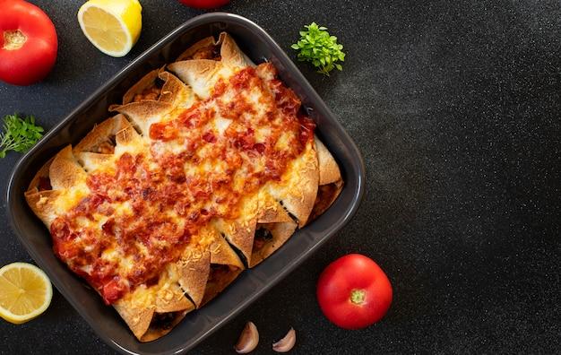 Meksykańskie enchiladas z kurczakiem, warzywami, kukurydzą, fasolą, sosem pomidorowym i serem. podawane na blasze do pieczenia. meksykańskie jedzenie. kuchnia latynoamerykańska. czarne tło, widok z góry, miejsce