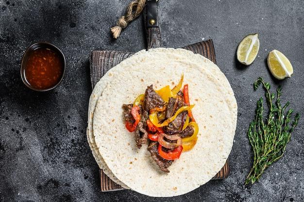 Meksykańskie fajitas z kolorową papryką i cebulą, podawane z tortillami i salsą.