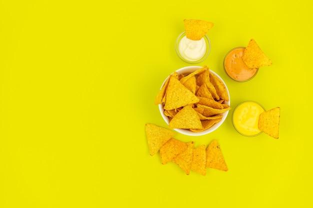 Meksykańskie jedzenie. chipsy tortilla w białym talerzu na kolorowym tle z sosem do maczania.