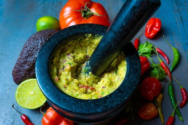 Meksykańskie jedzenie guacamole na moździerzu z warzywami i teksturowanym tłem
