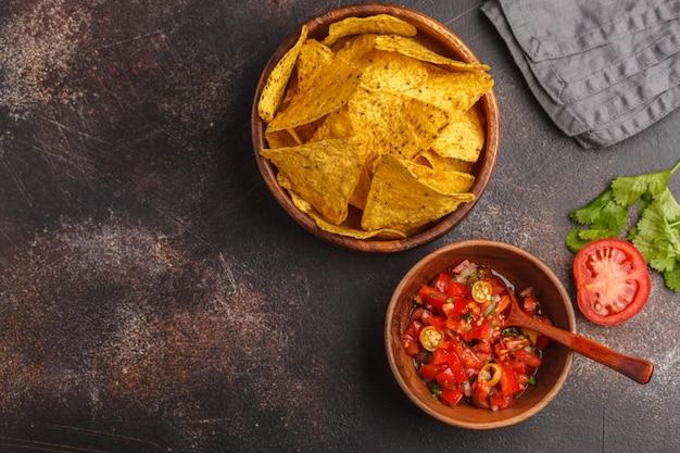 Meksykańskie jedzenie koncepcja. nachos - żółte płatki kukurydziane totopos z sosem pomidorowym pico del gallo, widok z góry, miejsce na kopię.