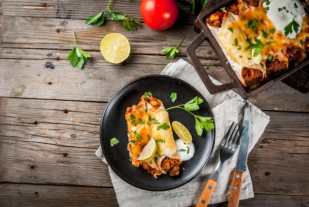 Meksykańskie jedzenie. kuchnia ameryki południowej. tradycyjne danie z pikantnych enchilad wołowych z kukurydzą, fasolą, pomidorem. na blasze do pieczenia, na starym rustykalnym drewnianym tle. skopiuj widok z góry