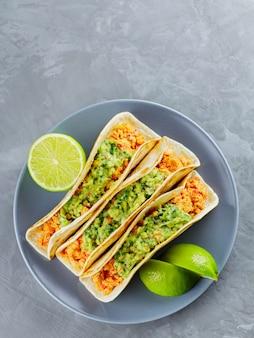 Meksykańskie jedzenie. tacos ze smażonym mięsem mielonym i guacamole na szarym talerzu. meksykańskie tacos i plastry limonki na szarym tle. skopiuj miejsce. widok z góry