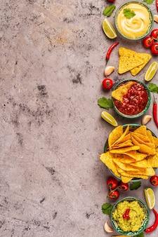 Meksykańskie jedzenie w tle: guacamole, salsa, serowe sosy z nachos, widok z góry.