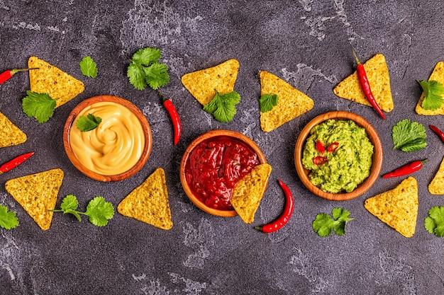 Meksykańskie jedzenie w tle: guacamole, salsa, serowe sosy ze składnikami na czarnym tle, widok z góry.