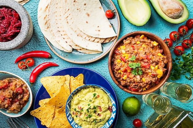 Meksykańskie jedzenie wymieszaj nachos, fajitas, tortilla, guacamole i sosy salsa i składniki na niebieskiej powierzchni. widok z góry