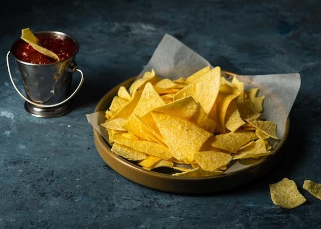Meksykańskie nachos z pomidorowym sosem keczupowym. koncepcja kuchni meksykańskiej. żółte kukurydziane chipsy totopos z sosem