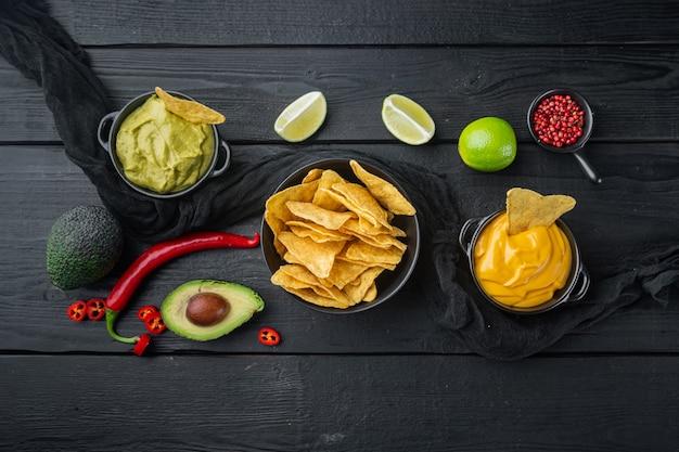 Meksykańskie nachos z sosem na czarnym drewnianym stole, widok z góry lub leżak na płasko