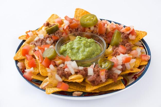 Meksykańskie nachos z wołowiną, guacamole, sosem serowym, papryką, pomidorem i cebulą na talerzu