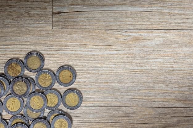 Meksykańskie peso na drewnianej powierzchni