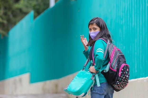 Meksykańskie powitanie dziewczyny z dystansem społecznym po powrocie do szkoły po pandemii koronawirusa