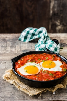 Meksykańskie śniadanie: huevos rancheros na żelaznej patelni na drewnianym stole