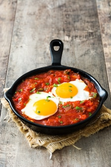 Meksykańskie śniadanie huevos rancheros na żelaznej patelni na drewnianym stole
