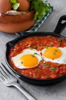 Meksykańskie śniadanie huevos rancheros na żelaznej patelni na szarym kamieniu