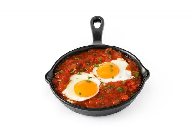 Meksykańskie śniadanie huevos rancheros w żelaznej patelni na białym tle