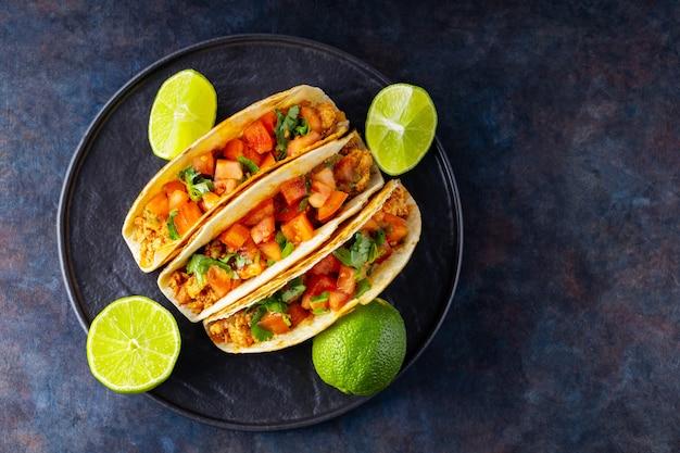 Meksykańskie taco i limonki na ciemnym tle. tacos z mieloną wieprzowiną, pomidorami i ziołami. taco z mięsem i warzywami na czarnym talerzu. skopiuj miejsce. widok z góry