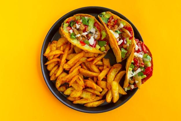 Meksykańskie taco z francuskimi ziemniakami na żółtym tle