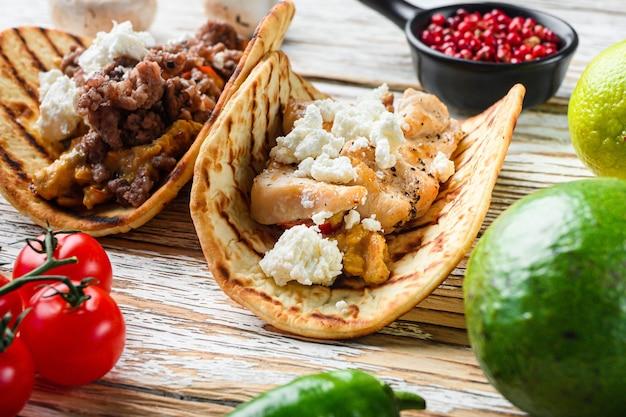 Meksykańskie taco z mięsem z kurczaka i dodatkami, na białym drewnianym tle