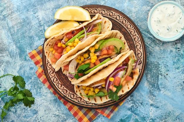 Meksykańskie tacos z grillowanym kurczakiem, awokado, ziarnami kukurydzy, pomidorem, cebulą, kolendrą i salsą przy niebieskim kamiennym stole. tradycyjne meksykańskie i latynoamerykańskie jedzenie uliczne. widok z góry.