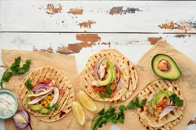 Meksykańskie tacos z grillowanym kurczakiem, awokado, ziarnami kukurydzy, pomidorem, cebulą, kolendrą i salsą stary biały drewniany stół. tradycyjne meksykańskie i latynoamerykańskie jedzenie uliczne. widok z góry.