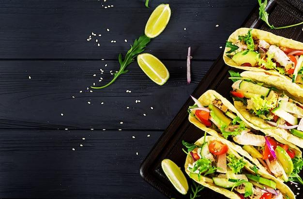 Meksykańskie tacos z kurczakiem, awokado, pomidorem, ogórkiem i czerwoną cebulą.