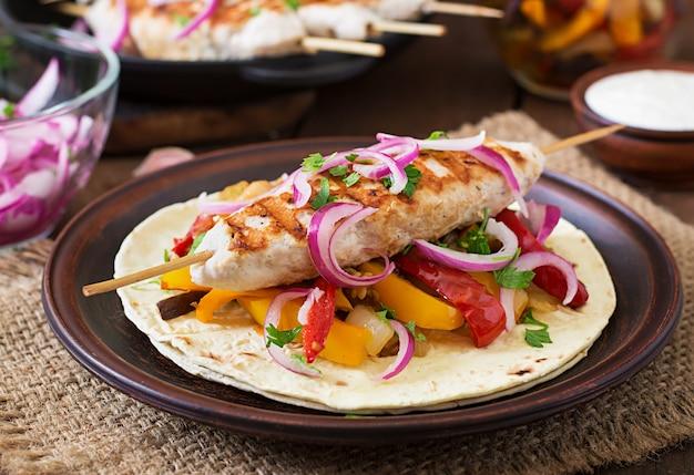 Meksykańskie tacos z kurczakiem, grillowanymi warzywami i czerwoną cebulą.