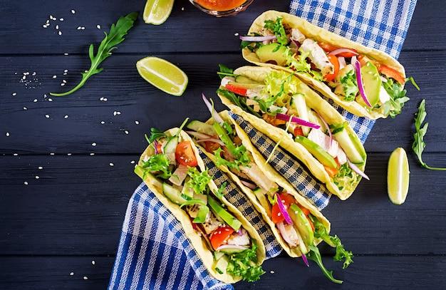 Meksykańskie tacos z mięsem z kurczaka, awokado, pomidorem, ogórkiem i czerwoną cebulą.