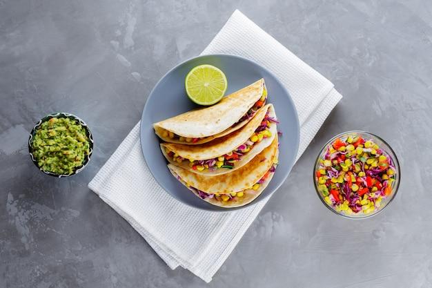 Meksykańskie tacos z warzywami i guacamole na szarym tle. wegańskie tacos z kukurydzą, fioletową kapustą i pomidorami na szarym talerzu. skopiuj miejsce. widok z góry