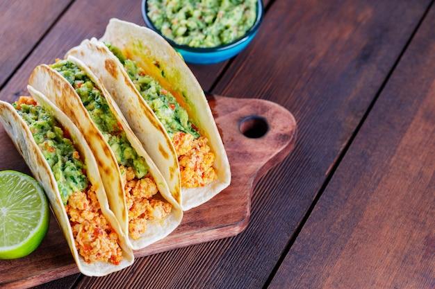 Meksykańskie tacos ze smażonym mielonym kurczakiem i sosem guacamole na drewnianych deskach. tacos, guacamole i limonka na drewnianym tle. kuchnia meksykańska