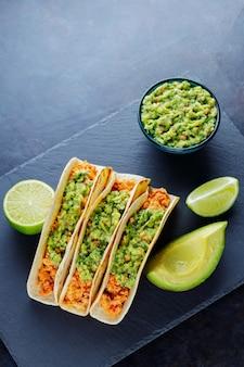 Meksykańskie tacos ze smażonym mięsem mielonym. tacos z kurczakiem i guacamole na ciemnym tle. tradycyjna kuchnia meksykańska. skopiuj miejsce. widok z góry