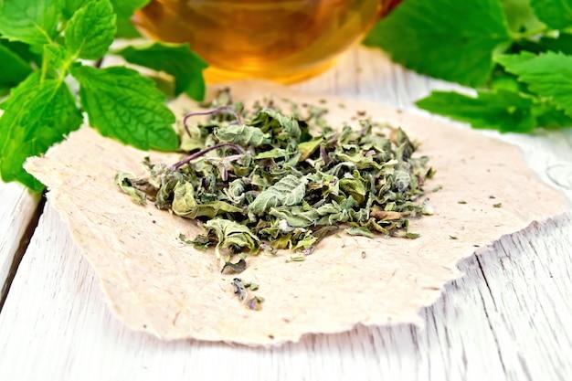 Melissa suszona na papierze, świeże liście szałwii, herbata w szklanym kubku na tle jasne drewniane deski