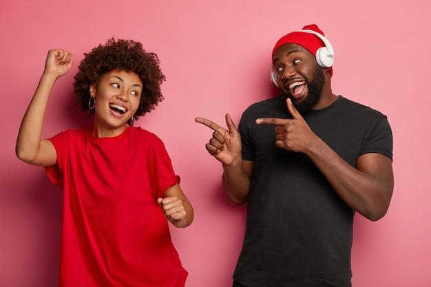 Melodia zmienia nastrój i doprowadza mnie do tańca. szczęśliwa zrelaksowana afroamerykańska kobieta tańczy zrelaksowana na imprezie dyskotekowej, chłopak wskazuje na nią