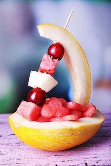 Melon, arbuz i śliwka w skórce melona na drewnianym stole na naturalnym
