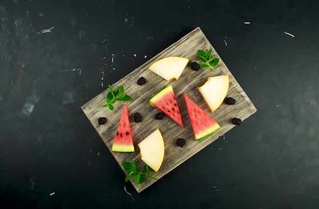 Melon, arbuz, jeżyny i mięta na drewnianym stole