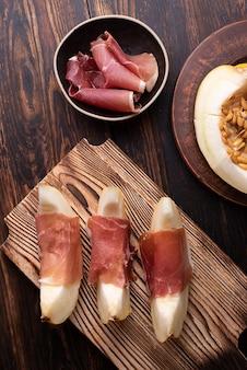 Melon i prosciutto crudo przystawka, świeża włoska szynka z plastrami owoców na ciemnym tle drewnianych.