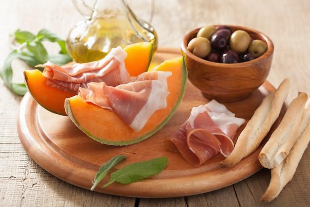 Melon kantalupa z szynką prosciutto i oliwkami. włoska przekąska