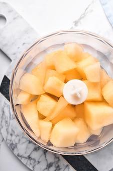 Melon. kawałki melona do robienia deserów owocowych w blenderze spożywczym przygotowane do przygotowania soku lub prawidłowego odżywiania na marmurowym białym tle. makieta. widok z góry.