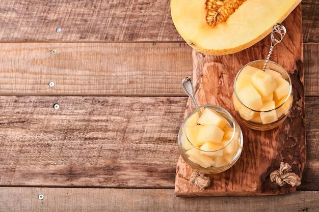 Melon. kawałki świeżego melona do robienia deserów owocowych w szkle na stare drewniane tła. makieta. widok z góry.