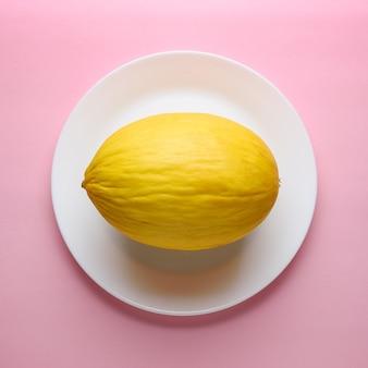 Melon na pastelowo różowej powierzchni.