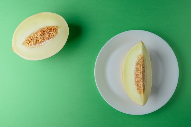 Melon pokrojony na jasnozielonej powierzchni.