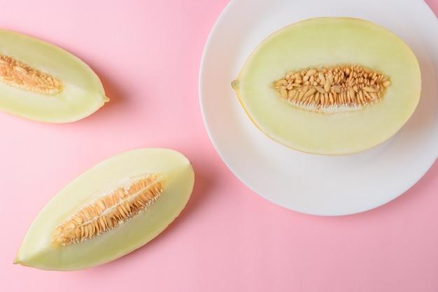 Melon pokrojony na pastelowo różową powierzchnię.
