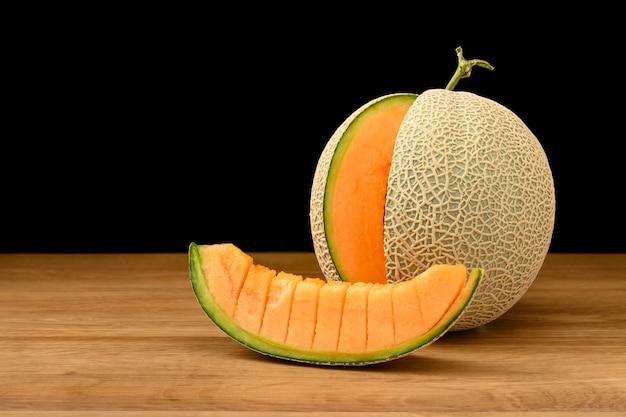 Melonowa owoc pokrajać na drewnianym stole z czarnym tłem