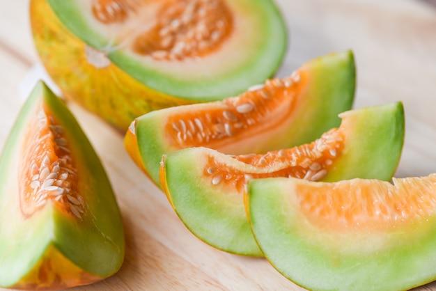 Melonowy kolor żółty - muskmelon pokrajać kantalupa tajlandzkiego tropikalnego owocowego azjata na drewnianym tle